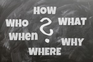 """A chalkboard with the following words written on it: """"How? What? Why? Where? When? Who?"""""""