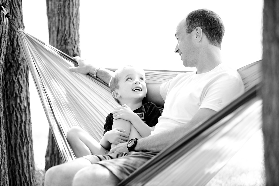 father and son smiling at each other on a hammock