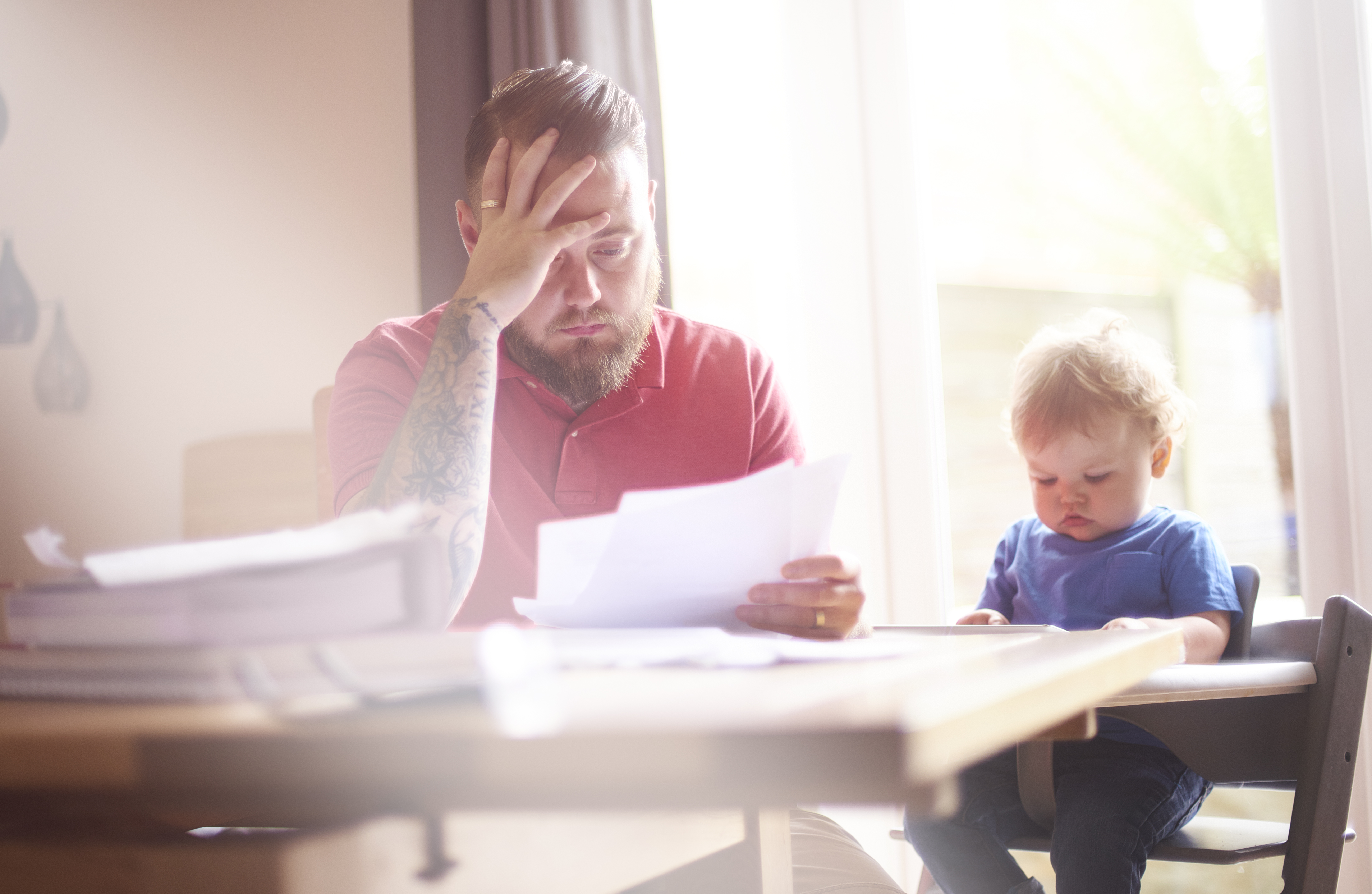 A father sits with his toddler at the dining table. He is reading through his latest bank statements and final demands. He his head in his hands trying to work out how to settle his financial difficulties. His son is sat in his highchair next to him.