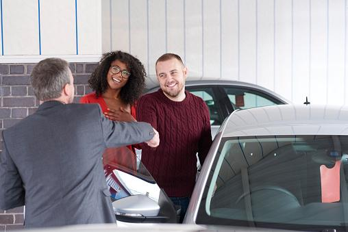 Couple shaking hands after buying a vehicle