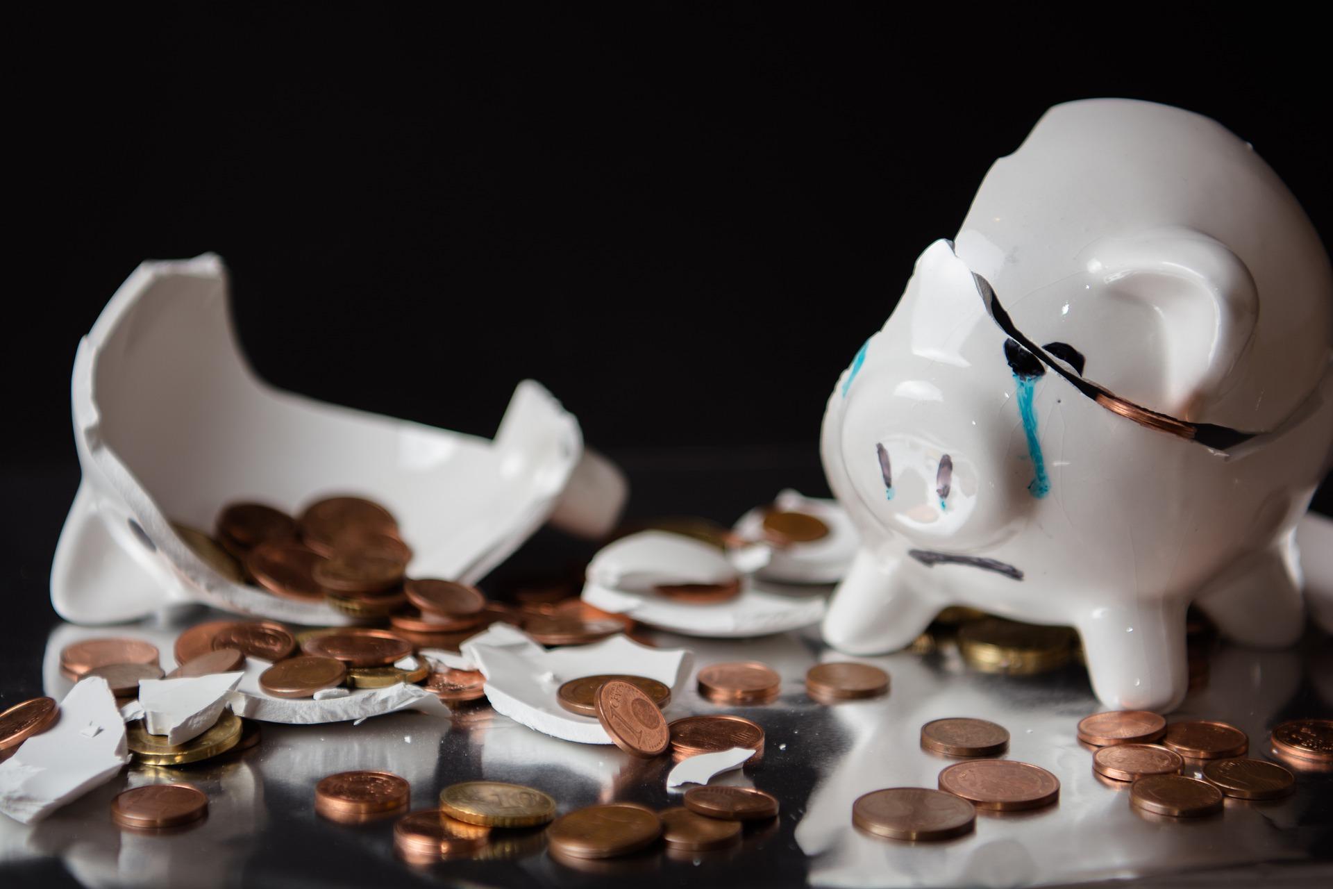 Broken piggy bank with coins everywhere